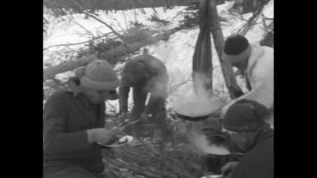 dog sled comes towards and past camera / dogs resting and men eating around fire / men cooking and eating around fire / men stand in group near dog... - 探検家点の映像素材/bロール