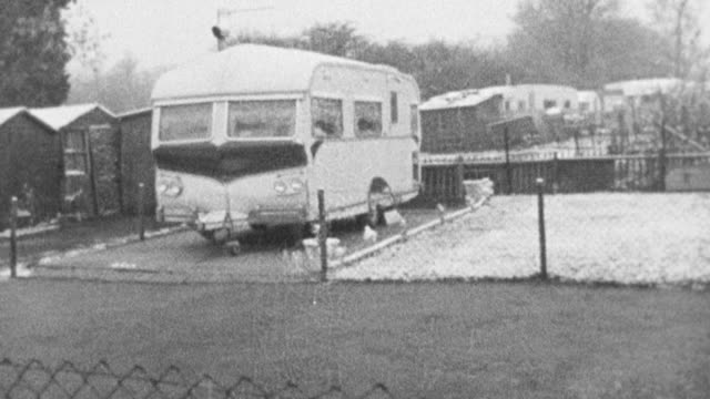 vidéos et rushes de 1972 montage dog standing against fence and walking past trailers, and child looking out of gypsy trailer window as mother closes trailer door / bushey, england, united kingdom - minorité
