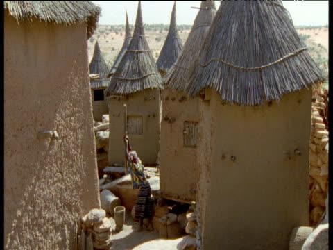 dogon woman pounds millet in front of huts, mali - tetto di paglia video stock e b–roll