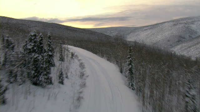 A dogsled trail winds through the Yukon mountains.