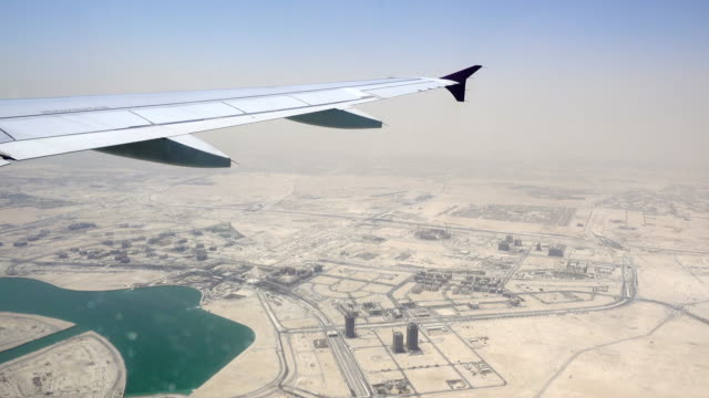 doha, qatar cityscape taken from airplane window with wing - qatar stock videos & royalty-free footage
