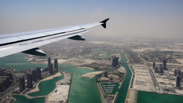 doha, qatar seen from airplane window with wing - tower stock videos & royalty-free footage
