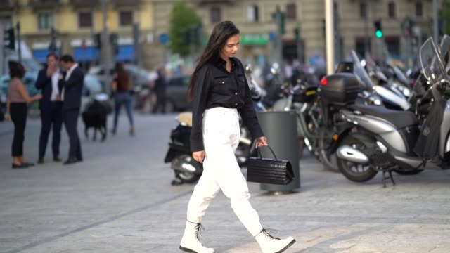 doina ciobanu wears a black shirt, white pants, leather boots with black shoelace, a leather crocodile pattern bag, outside the alberta ferretti show... - street style stock videos & royalty-free footage