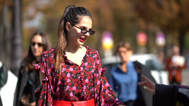 Doina Ciobanu wears a flower print top a red leather skirt red boots outside Issey Miyake during Paris Fashion Week Womenswear Spring/Summer 2018 on...