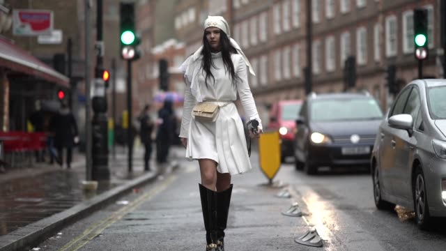 doina ciobanu wears a hat, a white ruffled dress, a belt bag from jw anderson, high boots, holds a camera, during london fashion week february 2019... - street style stock videos & royalty-free footage