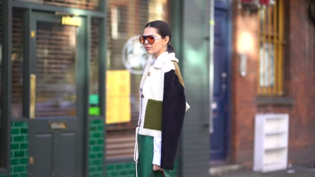 doina ciobanu wears a jw anderson brown bag green flare cropped pants a pull over a white shirt shoes sunglasses during london fashion week february... - london fashion week stock videos and b-roll footage