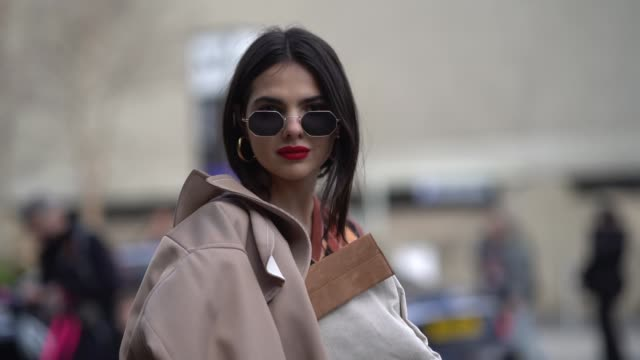 doina ciobanu wears a trench coat beige pants red gloves sunglasses a sleeveless pull over red shoes during london fashion week february 2018 on... - london fashion week stock videos and b-roll footage