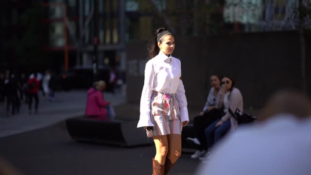 vídeos y material grabado en eventos de stock de doina ciobanu wears a white shirt, a pale blue and pink striped skirt, pink sunglasses, a brown leather boots, during london fashion week september... - camiseta