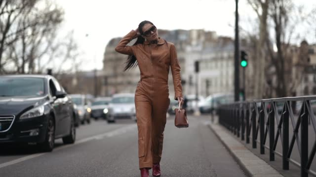 doina ciobanu wears earrings sunglasses a gold leather jumpsuit a brown handbag red alligator pattern boots outside redemption during paris fashion... - jumpsuit stock videos & royalty-free footage