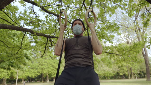 doing pull-ups in the park during social distancing - pull ups stock videos & royalty-free footage
