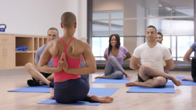 doing reverse prayer pose in a fitness class - mudra stock videos & royalty-free footage