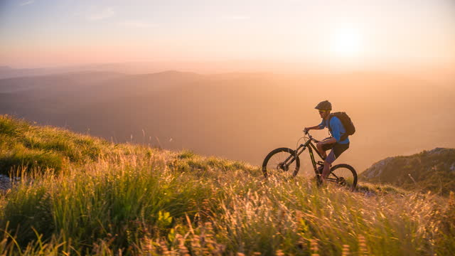 doing sports outdoors in nature, mountain biking uphill, surrounded by green meadows and mountains at sunset - mountain biking stock videos & royalty-free footage