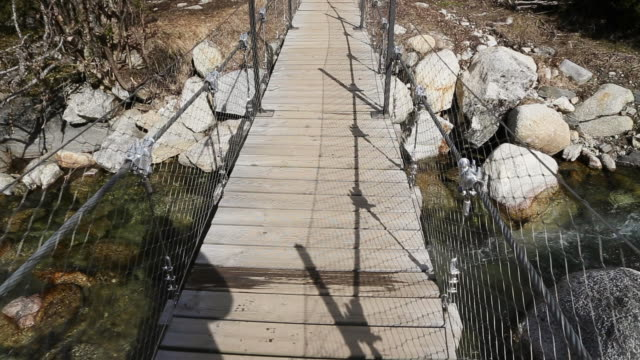 vídeos de stock e filmes b-roll de doing trekking from personal point of view walking on the aiguestortes national park in the catalan pyrenees. - ponte suspensa
