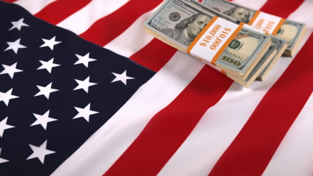 Dollar Bank Notes falling on American Flag, slow motion 4K