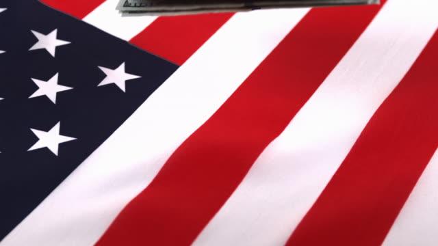vidéos et rushes de dollar bank notes falling on american flag, slow motion 4k - groupe moyen d'objets