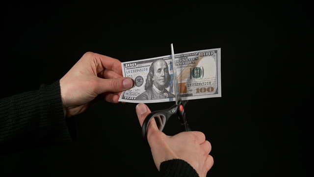 1 US Dollar Banknote with a pair of scissors against Black Background, Real Time 4K