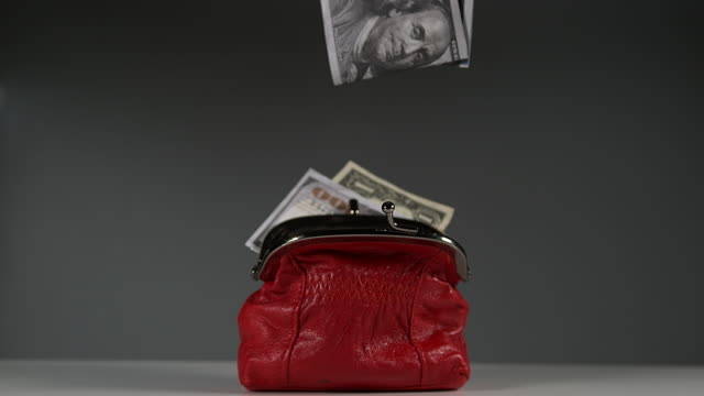 Dollar Banknotes falling into Red Purse, Slow motion 4K