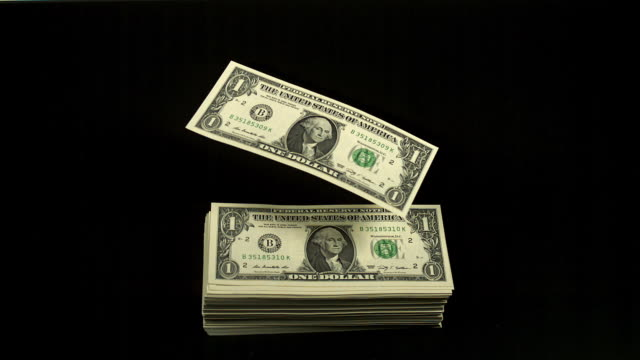'1 US Dollar Banknotes flying against Black Background, Slow Motion'