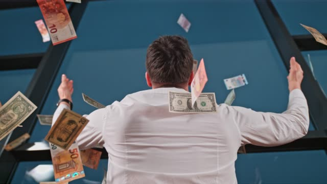 US dollar bills and Euro banknote falling over businessman at office window, super slow motion