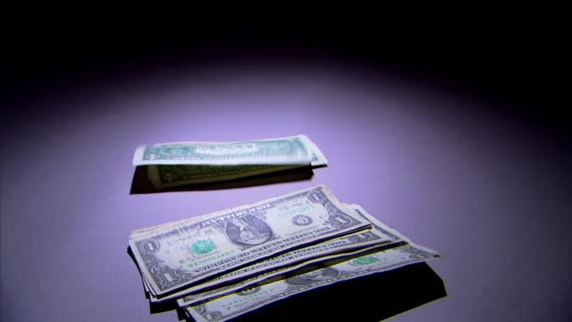 dollar bills fall to a spotlighted surface. - banconota da 10 dollari statunitensi video stock e b–roll