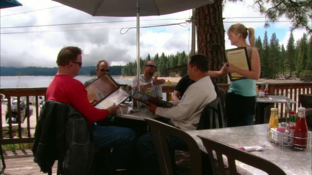 vidéos et rushes de ms dolly across restaurant deck as waitress gives menus to five men at table/ fresno county, california - fresno