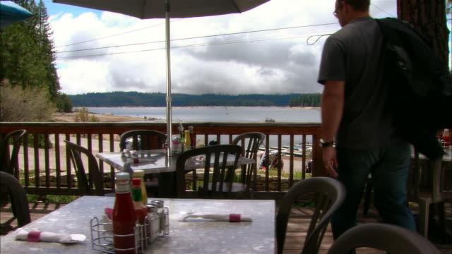 vídeos de stock e filmes b-roll de ws dolly across restaurant deck w/ view of lake + forest as five men sit down at table/ fresno county, california - sentar se