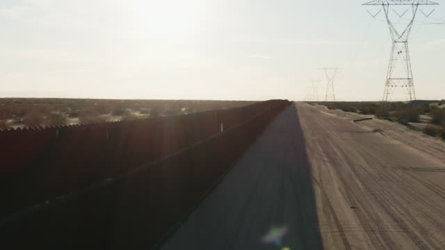 dolly aerial drone shot of flying over the steel-slat border wall and a dirt road (on the us side) between mexico and the united states on a bright, sunny afternoon - international border barrier stock videos & royalty-free footage