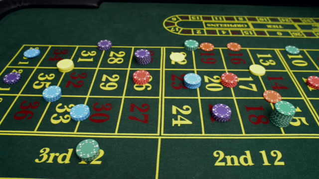 dolly along roulette table with chips and croupier - casino worker stock videos and b-roll footage