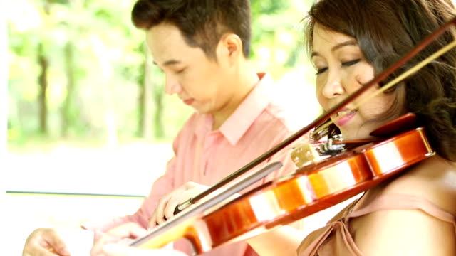 vídeos de stock, filmes e b-roll de dolly: asian feminino violinistas tocando violino com o namorado de audição - teatro clássico