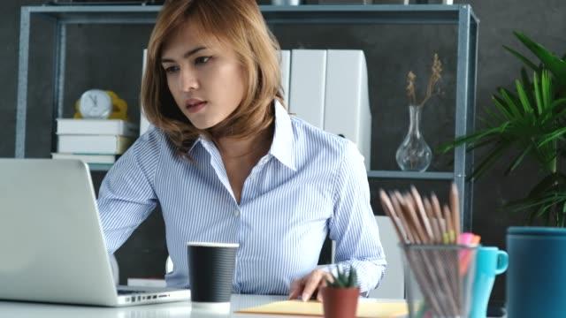 vídeos y material grabado en eventos de stock de dolly: mujer asiática trabajando en casa - camisa