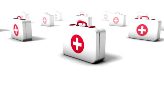 dolly back diagonally from single first aid kit revealing many - första hjälpen sats bildbanksvideor och videomaterial från bakom kulisserna