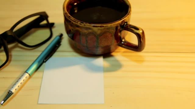 Transportwagen Kamera Aufnahme :  Weißem Papier mit eine Tasse Kaffee, Kugelschreiber und Gläser.