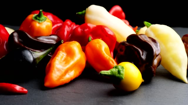 dolly: different chili peppers on black - peperoncino video stock e b–roll