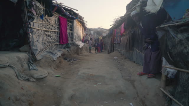 Dolly down pathway in Kutupalong refugee camp in Bangladesh as people peek out of their homes at the camera Fleeing persecution by the Myanmar...