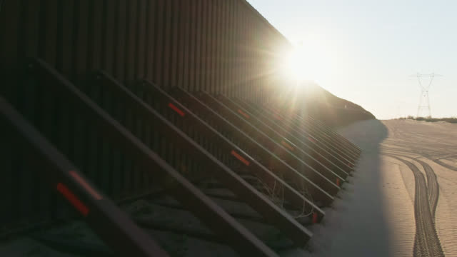dolly drone shot of the steel-slat border wall and its supports (on the us side) between mexico and the united states on a clear, sunny day at sunset - surrounding wall stock videos & royalty-free footage