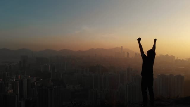 dolly forward of man standing and arm raise for celebration on mountain peak. - skyscraper stock videos & royalty-free footage