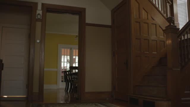 Dolly forward toward doorway of vintage dining room with lots of old oak woodwork.