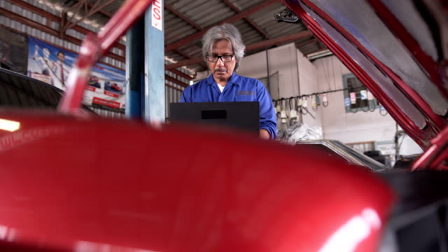 dolly from front view: Asian senior car mechanic Working on the laptop to fix the vehicle