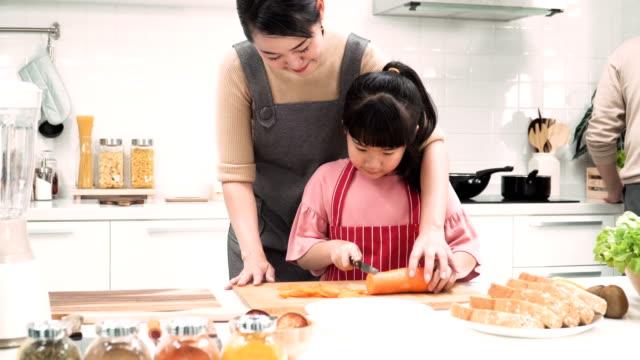 フロント ビューをドリー: 日本人母と娘一緒に台所でニンジンをチョッピング - 台所点の映像素材/bロール