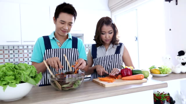 Dolly: Happy Couples preparing and cooking green vegetable salad