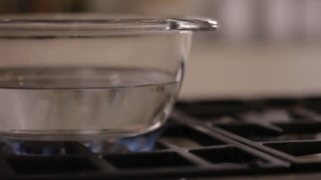 dolly in on a glass pot filled with water on a hob - boiling stock videos & royalty-free footage