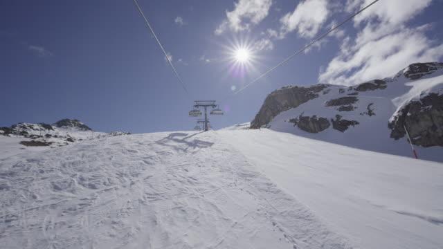 Dolly in ski lift along ski slope.