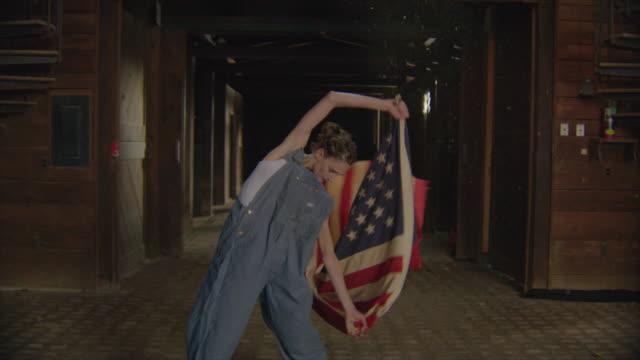 dolly jib arm shot of two dancers in wooden barn with american flags - アルスター郡点の映像素材/bロール