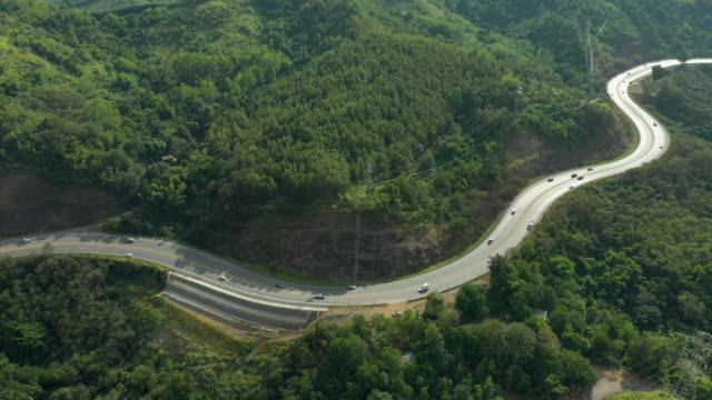 dolly left aerial view of road passing the mountain - mountain pass stock videos & royalty-free footage