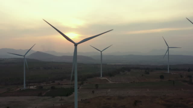 dolly left aerial view of wind turbine in sunset time - turning stock videos & royalty-free footage