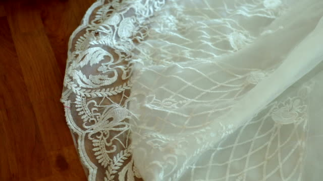 cu dolly left camera : detail of a white wedding dress hanging in the room. - coniugi video stock e b–roll