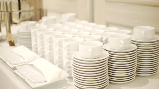 ms dolly left camera of white dishware stacks of clean cups and plates on the table indoors. - ceramics stock videos & royalty-free footage