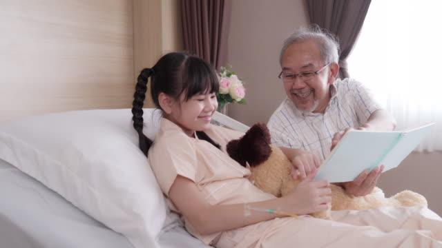 vidéos et rushes de 4k uhd dolly gauche: papa lecture histoire conte à la petite fille patiente à l'hôpital ward. concept de soins de santé hospitaliers. - histoire