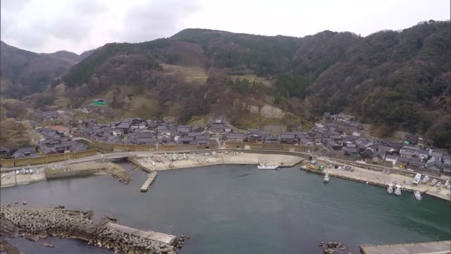 dolly left from magaki-no-sato; zoom back; wide shot covering ohzawa fishing port - multicopter stock videos & royalty-free footage