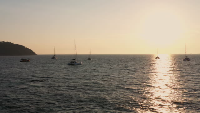 dolly links: gruppe von yachten, die bei sonnenuntergang auf dem meer schwimmen - anchored stock-videos und b-roll-filmmaterial